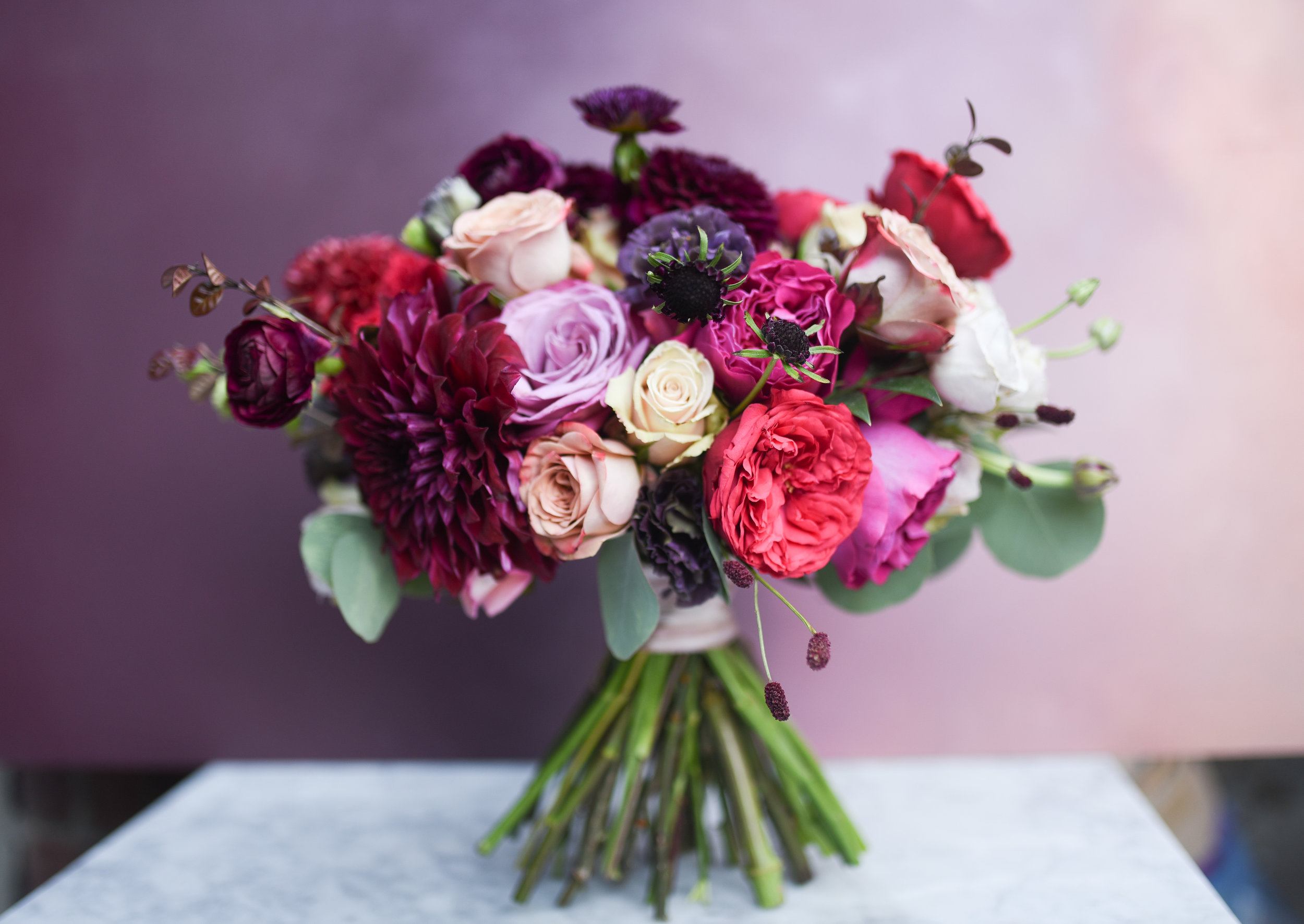 A hand tied bridal bouquet in jewel tones