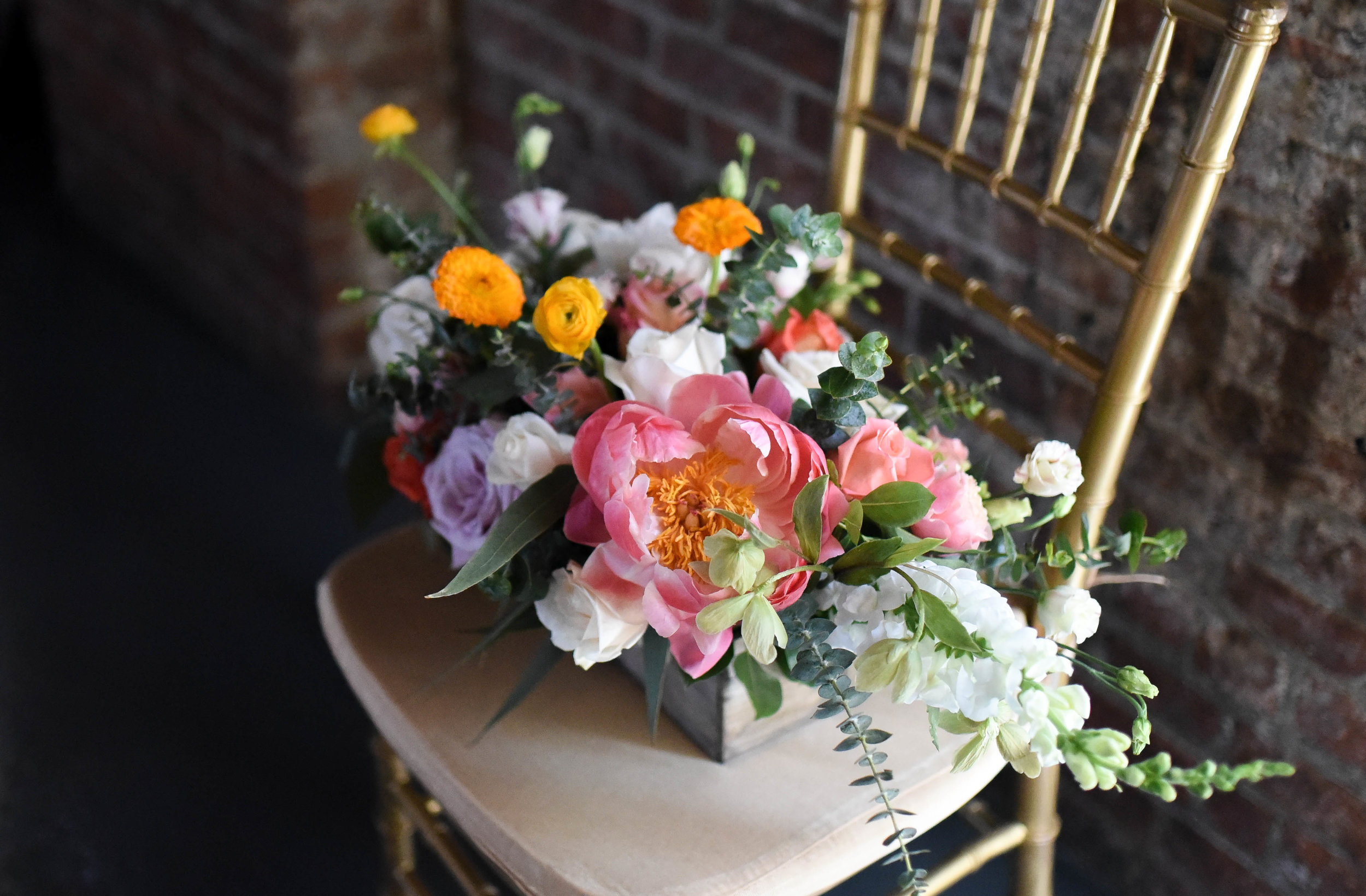 A gorgeous centerpiece with citrus tones paired with soft purples and eucalyptus
