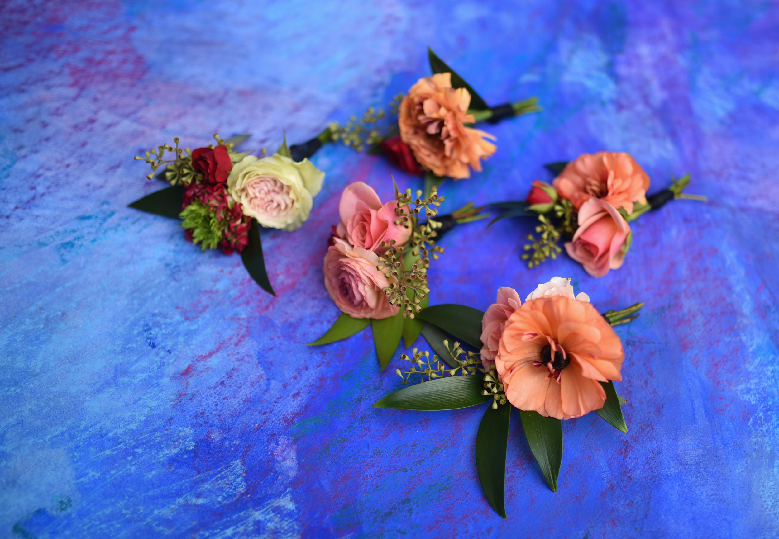 Saturated peaches and ruby reds were the focus colors in the boutonnieres