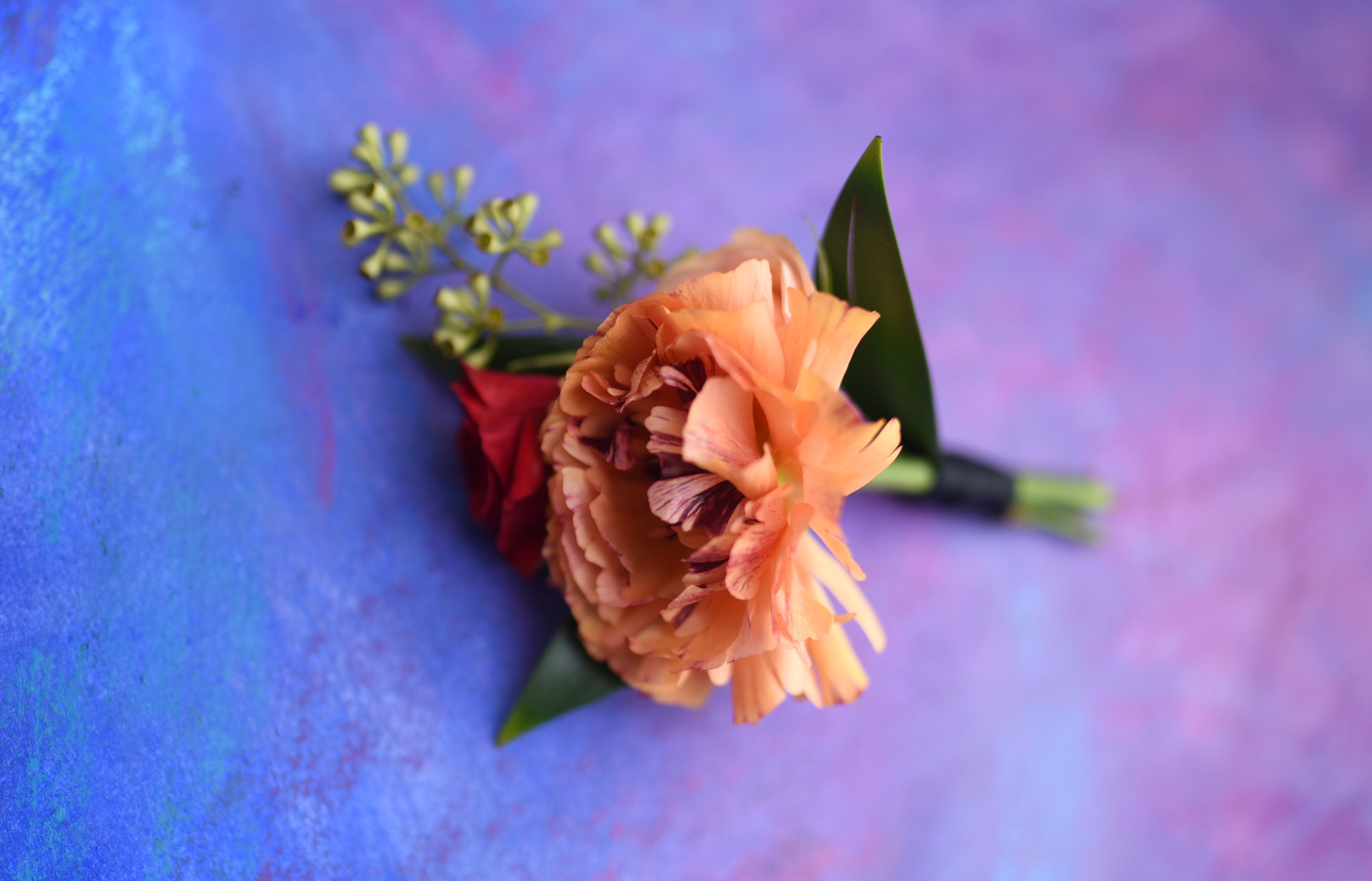 A close-up of the groom's boutonniere