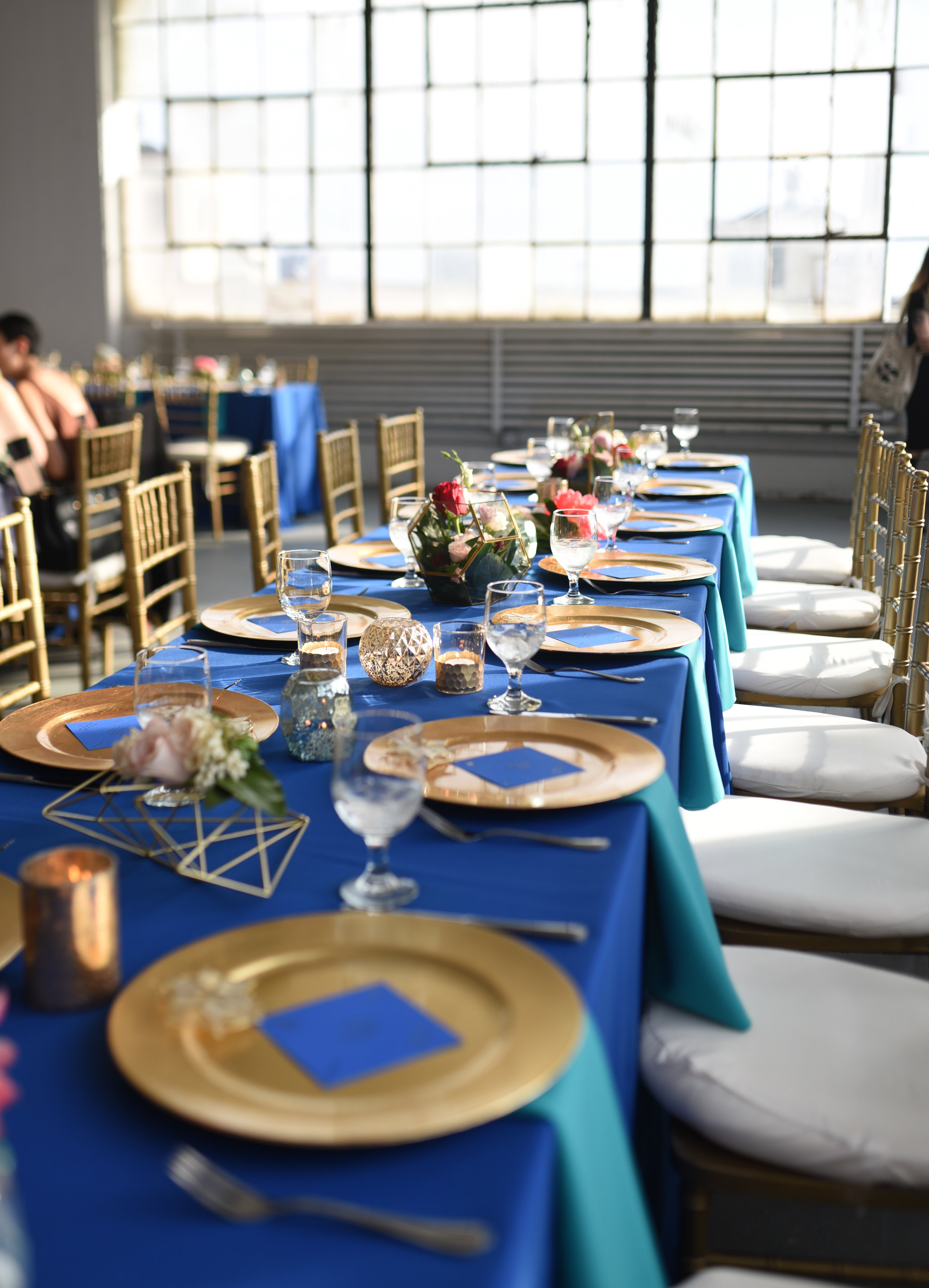 Spread through the center of the tables were floral terrariums, candles and lanterns, and geometric shapes with flower accents