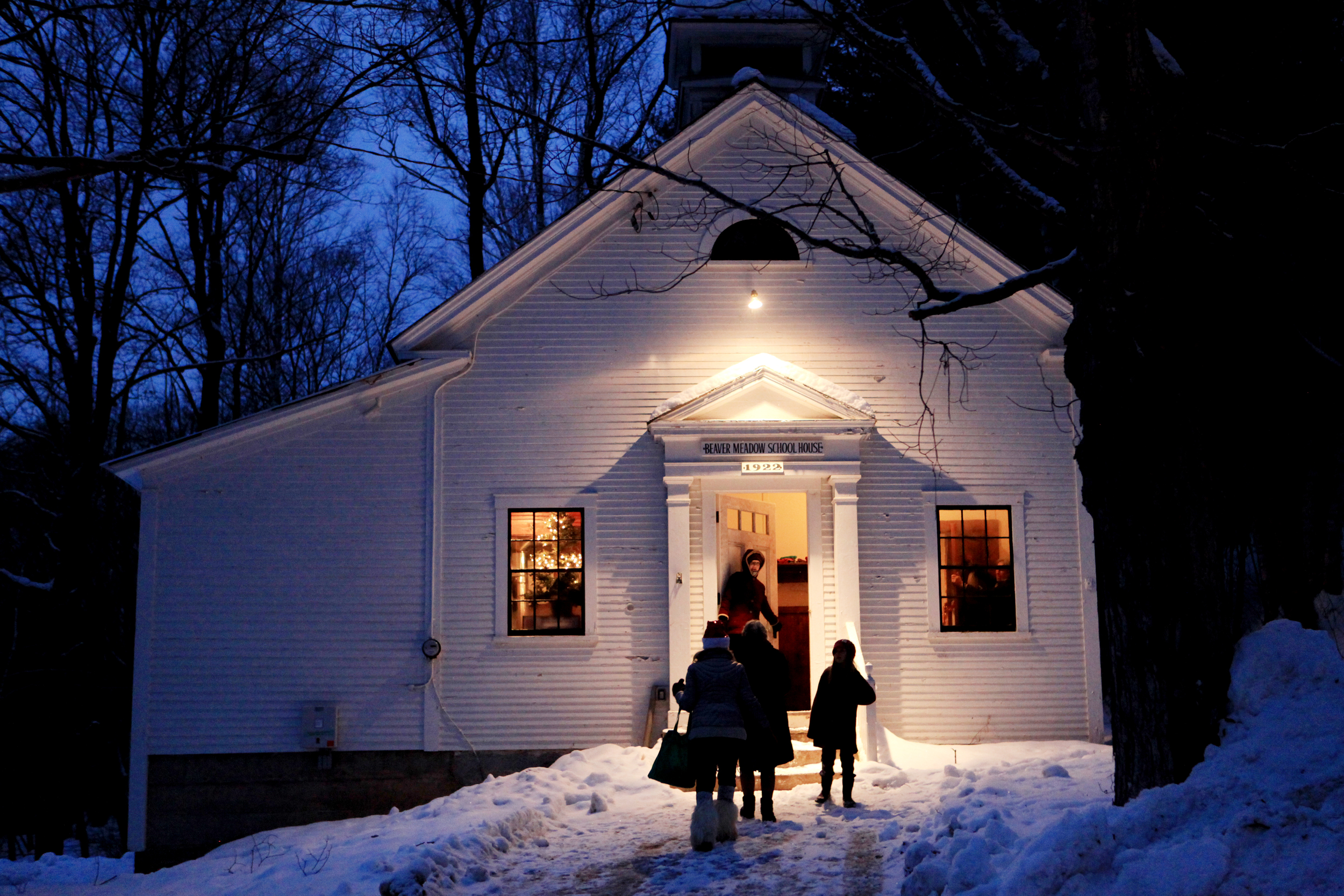 Light from the Beaver Meadow school house in Norwich, Vt. beckons those coming to the holiday service and potluck on Dec. 21, 2014.