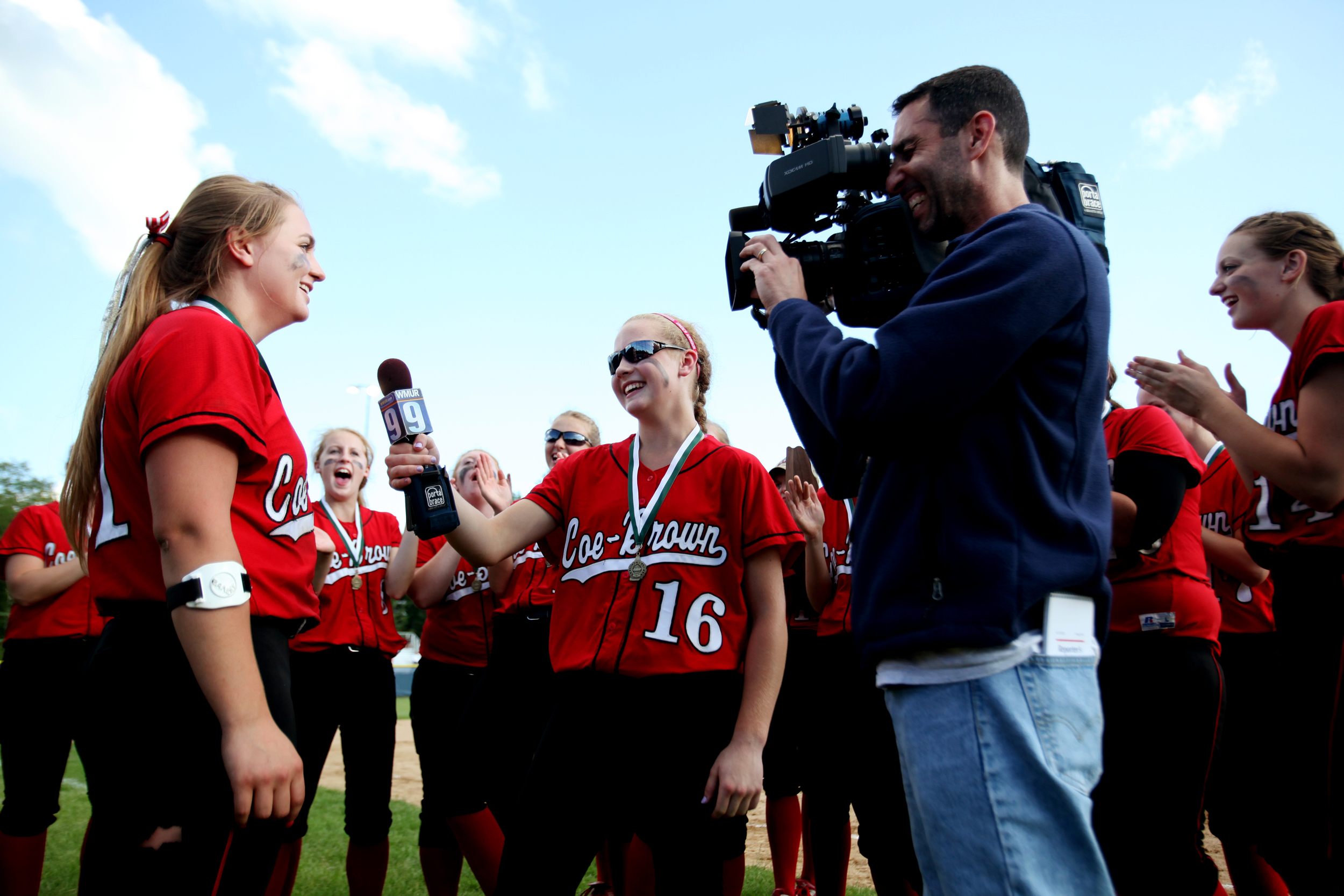 Coe-Brown's Catherine Langdon (middle) holds the microphone to teammate Lauren Jones as she is interviewed by WMUR's Jon Arnold after they won the Division II softball championship against John Stark at Southern New Hampshire University in  Hooksett, N.H. on June 14, 2014. Coe-Brown won 6-5.