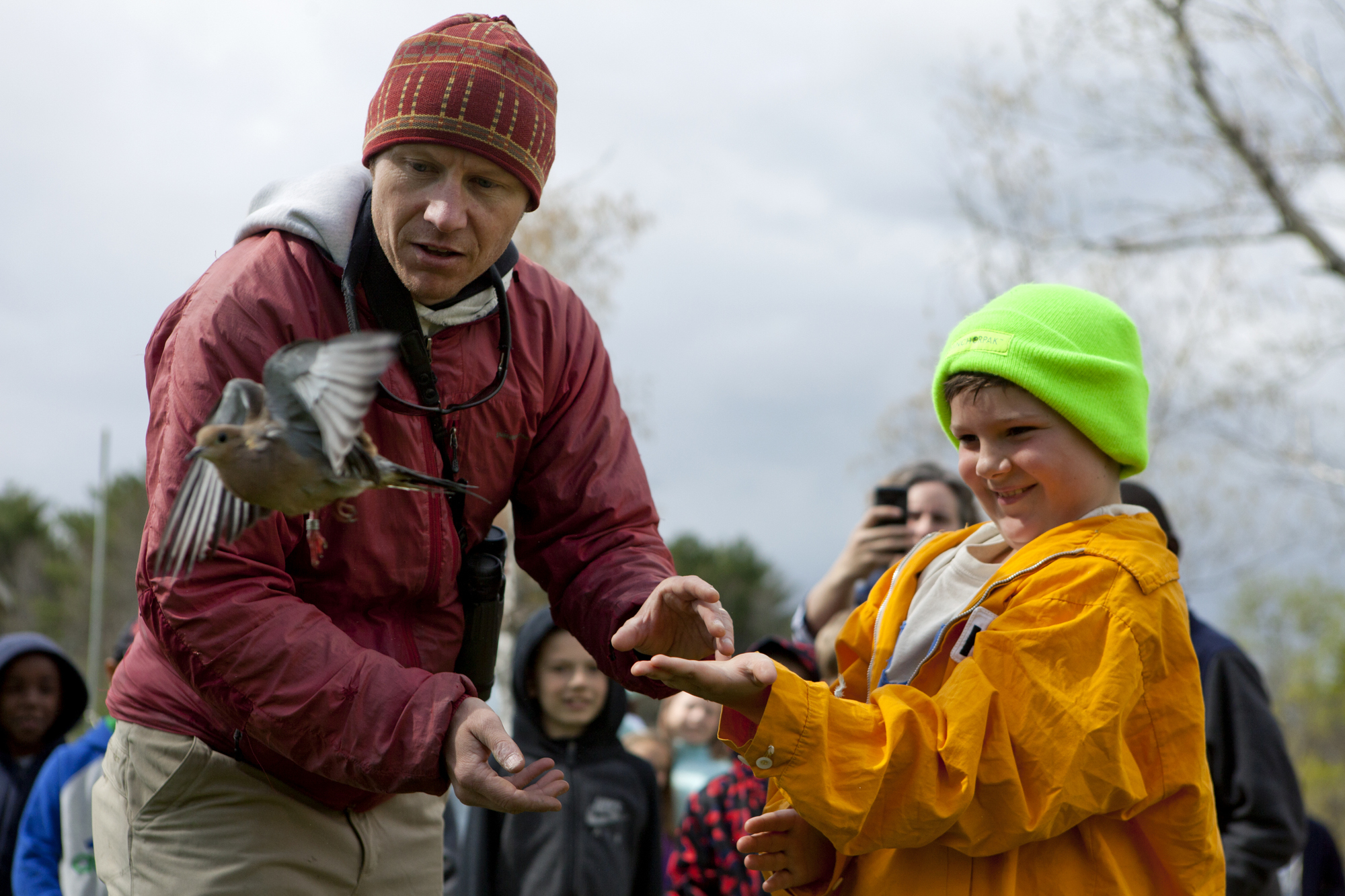 Biodiversity Research Institute's Patrick Keenan, and a Hall Elementary student release a Mourning Dove after it was banded and recorded by BRI volunteers in Falmouth, Maine on May 9.