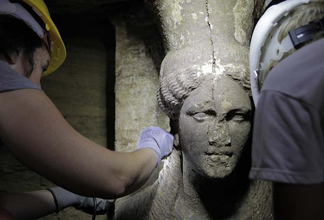 Greek Culture Ministry  Archaeologists this month inspect a female figurine on a wall leading to the main room of an ancient tomb in Amphipolis, northern Greece.