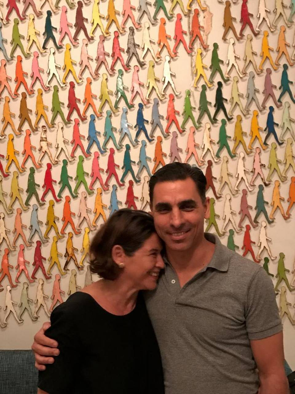 """Internationally known Cuban artist Damian Aquiles and his American wife, Pamela Ruiz, stand in front of his """"Walking Men"""" work, which was also commissioned by the Council on Foreign Relations office in Washington, D.C. Evolving political change in Cuba is giving artists and budding entrepreneurs a glimpse at new opportunities. - Markos Kounalakis"""