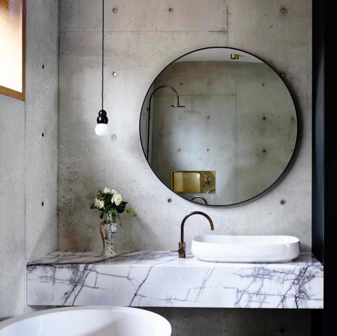 Marble vanity with brushed matt brass mixer matching the dark metal edge of the mirror.