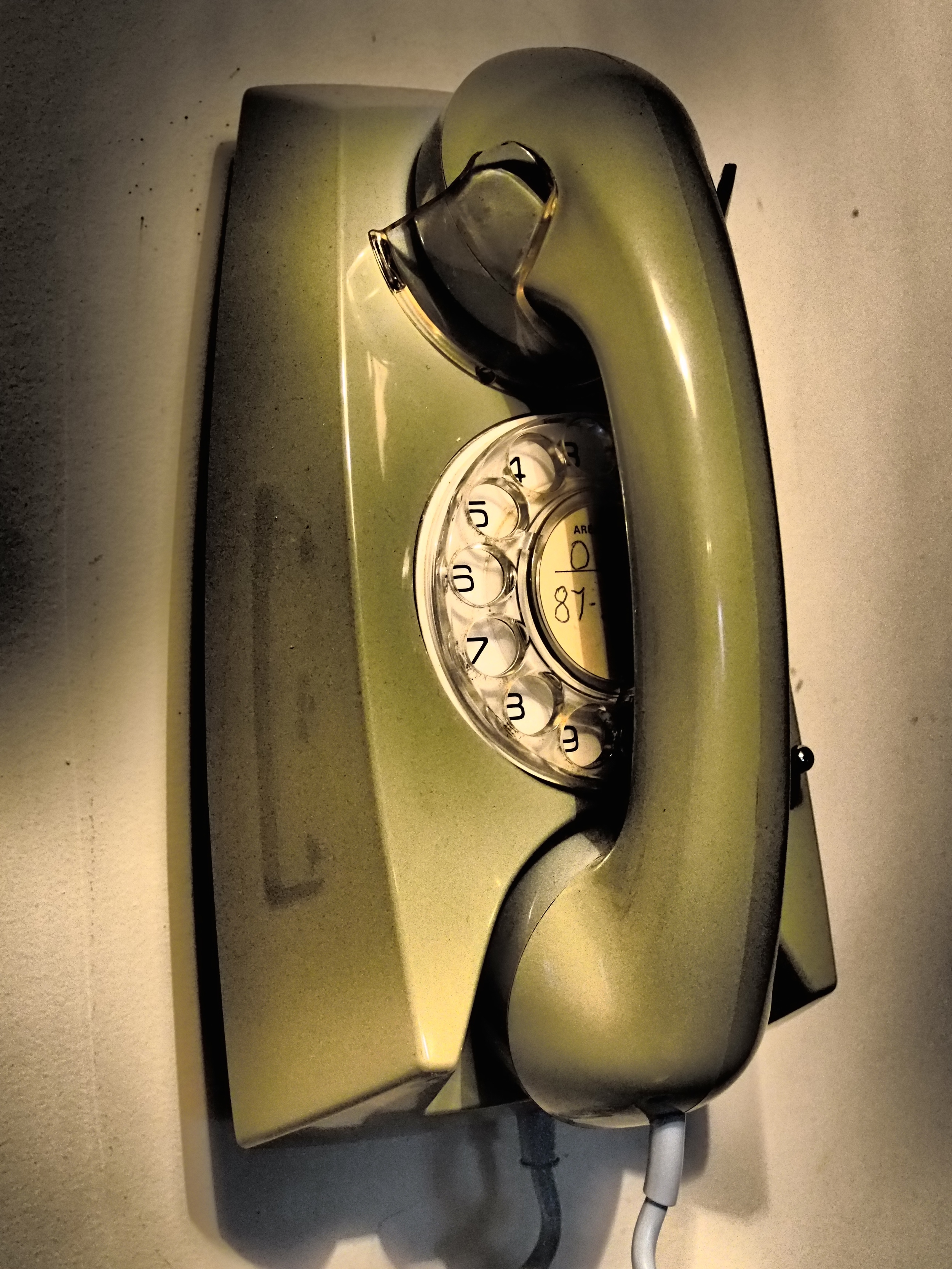 Old-fashioned green rotary telephone hanging from wall.