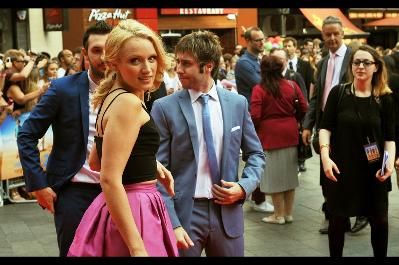 Emily Berrington is wearing a dress profoundly purple enough to draw the attention of (for now) two of our heroes. The other two are hastening for another photo opportunity, to the no-doubt chagrin of all the girls in the crowd.