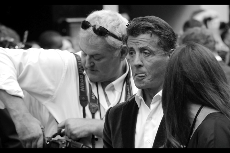 Sylvester Stallone can almost taste the free popcorn and cool refreshing hyper-tub of Coke.... and he only has a couple thousand people screaming for his autograph to sign for... if he can get past the popcorn....