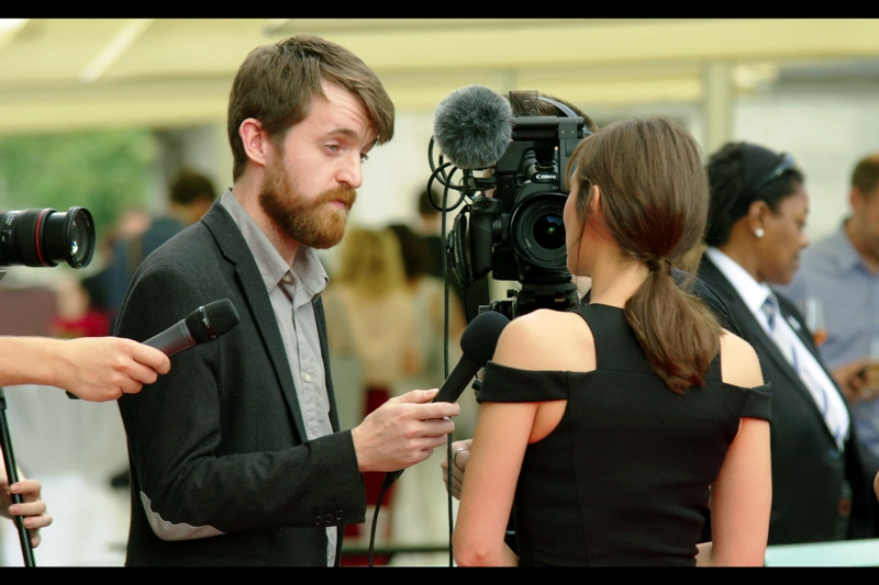 """""""You really think my shoulder patches complement my hair? Why thank you!"""". The brothers Dardenne have gone indoors, possibly to check out some of the exhibits on display at Somerset House, while Marion Cotillard flies solo on the red carpet, doing interviews. Her dress is black. That's all for now. (I hope she turns around eventually otherwise this is going to be a pretty sub-par journal even by my standards)"""