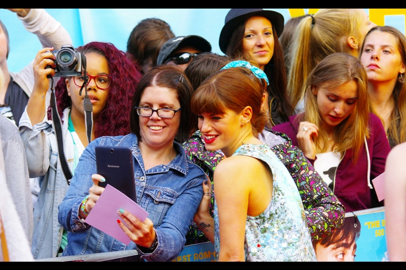 I'm not so much looking at Jemima Rooper, or the Fan looking at the fan's holiday pictures (or workplace spreadsheet or recipe for a better BananaBreadCakeSlice)... but the lady on the far left who is pointing her DSLR at nothing in particular (because Daniel Radcliffe is not where she's pointing)