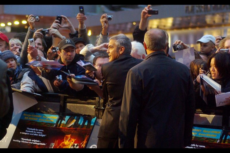 """"""" Check this out, I'm signing without even looking!""""  There is a reason why George Clooney is capable of this feat..."""