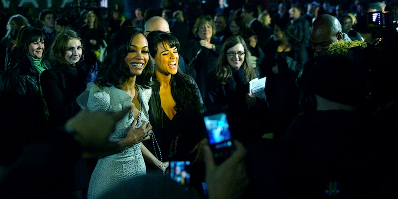 Zoe Saldana and Michelle Rodriguez share a laugh on the Red (okay, Blue) Carpet. Aussie Actor Sam Worthington, who was third to arrive, and at this point was STILL signing autographs in the first part of the crowd (which he later returned to)