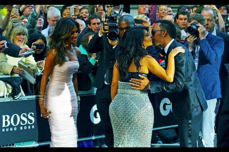"Well, who would have predicted this day would end (or at least include) a photo for Formula 1 racer Lewis Hamilton kissing Kim Kardashian while his singer girlfriend Nicole Scherzinger looks on, and her husband rapper Kanye West looks on. And... I look on . (Lewis Halmilton won the ""Sportsman"" award on the night, and without wanting to display anything but the highest regard for the GQ Awards, wasn't his last title back in 2008??)"