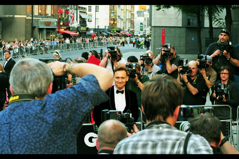 "Tom Hiddleston, actor. You may remember him from such crowd screams as ""OMG THAT'S TOM HIDDLESTON!!"". And if I had as much luck with women or money as I do simply photographing Tom Hiddleston regardless of vantagepoint, I'd be a millionaire and married to Charlize Theron by now."