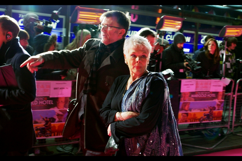 Dame Judi Dench muses over whether to step even slightly away from what little heat the bar heaters in the background provide just to sign some autographs for people crazy enough to wait out in the cold for her. I've never seen bar heaters at a premiere before....