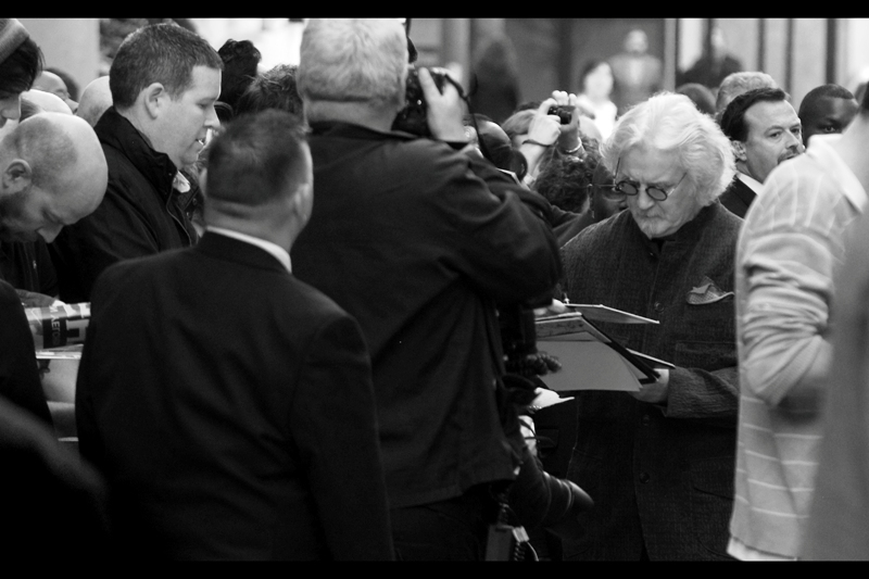 """""""That's not a spec script, that's a transcription of one of my standup routines... and it's not even that good, damnit"""". Billy Connolly is our first arrival, and he is wearing a brown jacket with green-rimmed circular glasses. That said, the photo still looks better in black'n'white."""
