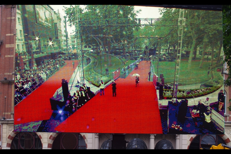View from a TV Screen across from me. Two prongs of the three-pronged red carpet (my spot was near the corner on the left, with a long view of the Batman cowl and stage). The forecast was for rain, autograph dealers and Marion Cotillard. And all three eventuated!