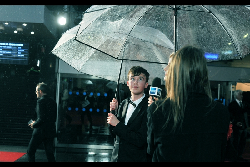 """The second umbrella is really helping. Thank you.""  Alex Lawther plays young Alan Turing in the film. And while the horde of excited young girls/women might ordinarily be into young heartthrobs, I'm pretty certain they're mostly to see the actor who plays ADULT Alan Turing in the film."