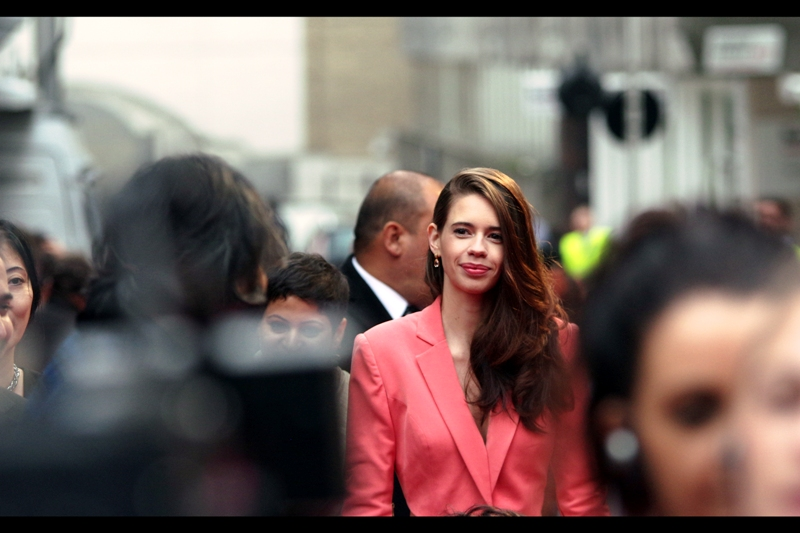 "This is not merely a random good-looking fashionable salmon-wearing Suit-jacked woman... this is Kalki Koechlin who is in the movie ""Margarita With A Straw"" which was ALSO having its (very brief) premiere at the same time. I'm not quite sure whether I like this ""Red Carpet As A Busy Airport Runway"" thing they're doing... but I tend to think I do."