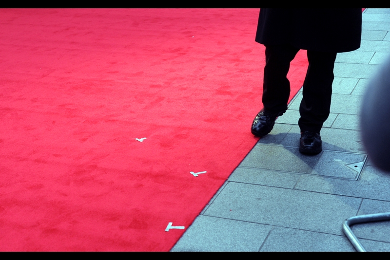 Contrary to (possible) popular belief, people don't just randomly stand on a red carpet to be interviewed or photographed. Sometimes there are markings on a carpet to show where people will stand. Alternatively, you have to be realistic... are you REALLY going to tell Professor Snape or Hans Gruber where he's meant to stand?