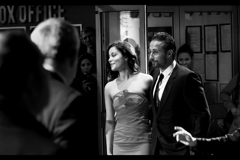 Matthias Schoenaerts has a girlfriend, and her dress is red and quite pretty. So... sorry about the black'n'white conversion if you wanted to know the precise shade for your records