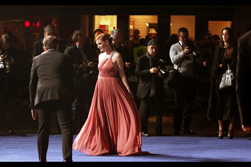 "Our third arrival is Jessica Chastain, who got a Best Actress nomination for 'Zero Dark Thirty', and was really good in the movie ""The Debt"". Her dress  I believe is best described as ""salmon"" coloured?"