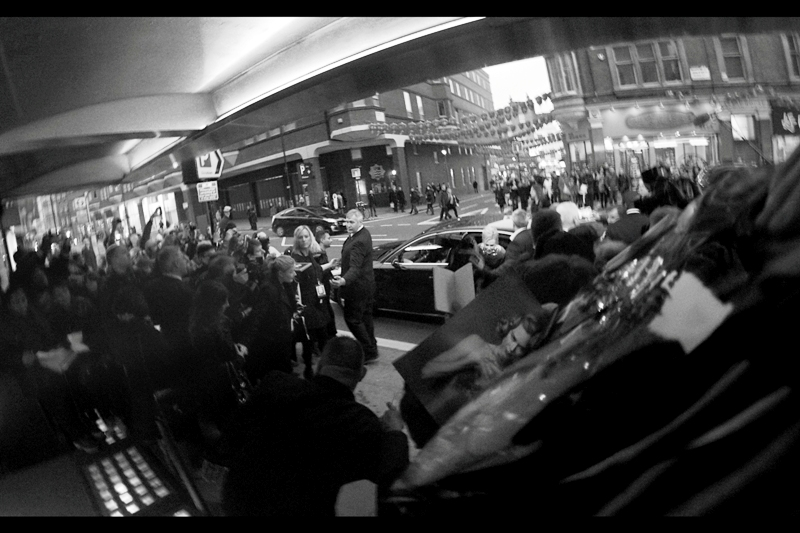 "A car pulls up and dispenses Nicole Kidman. Disturbingly, at ""last week's Baftas"" they had riot-control style barriers - chest high and heavy. In contrast at most premieres they have fairly robust waist-high metal fences. However, at this one they only had bank branch style ropes! ... which is barely one step up from trying to keep rabid autograph dealers (or a barracuda swarm) at bay with polite language."