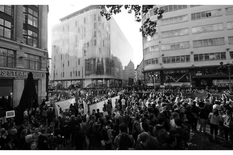 """I decide to at least keep moving. This is possibly my favourite 'compromise' shot - a shot I can't ordinarily take because I'm too close to the action. This shows some of the layout of the premiere - not just the fans, but also the huge multi-storey press stage, cars dropping off celebs, and also the queue of invited guests and ticket holders and their separate queue to walk the red carpet. I actually quite like the full-size image """" which is here in case you are interested """""""