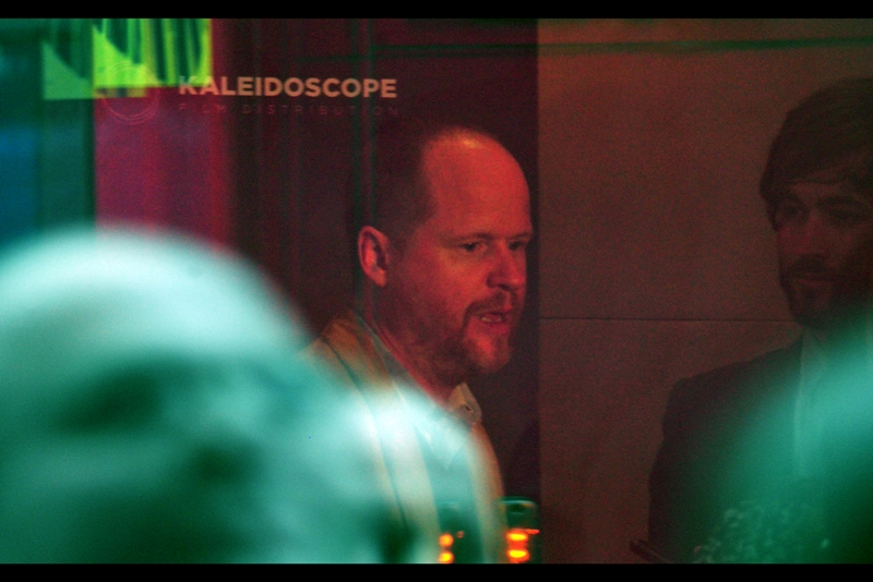 Desperate times. I'm photographing Joss Whedon through a window. Not something I'm excessively proud of. (Except for the other shot where he's reflected in a bus behind me.. that kind of works)