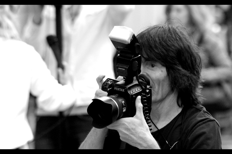 The man on the red carpet with the Sitting Down method of taking photos? Shoots PENTAX. And not just Pentax (because I shoot Pentax... it's totally a legitimte brand) but rather Pentax Medium Format Digital. Which is not only enough to put a whole lot of DSLRs to shame in terms of 40 megapixels on a giant sensor (at 1 frame per 1.1 seconds), but is like bringing a hand grenade to a game of scissors-paper-rock. ....  Albeit a very _slow_ hand grenade....