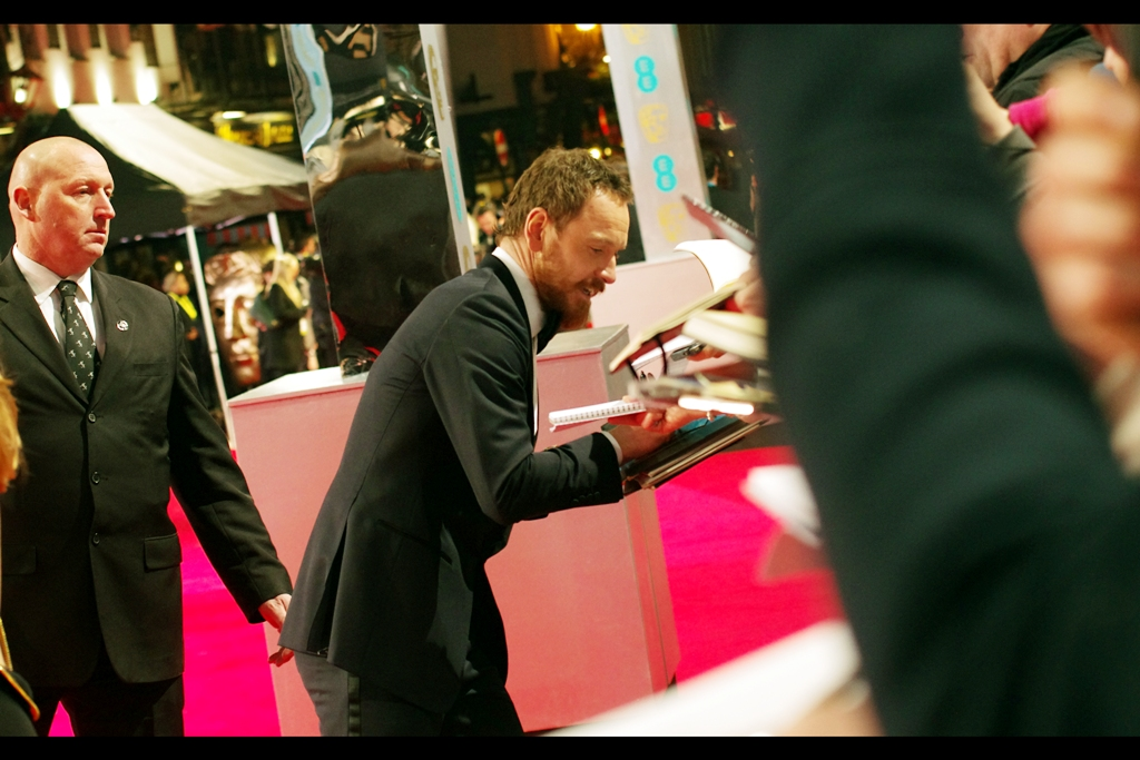 """Pay me later – I gotta get to my seat or they'll give it to a filler!""  Michael Fassbender dispenses a quick autograph. I heard an autograph dealer say he preferrd 'clean shaven' Fassbender, but given the dealers' general lack of hygiene I don't consider the criticism valid."