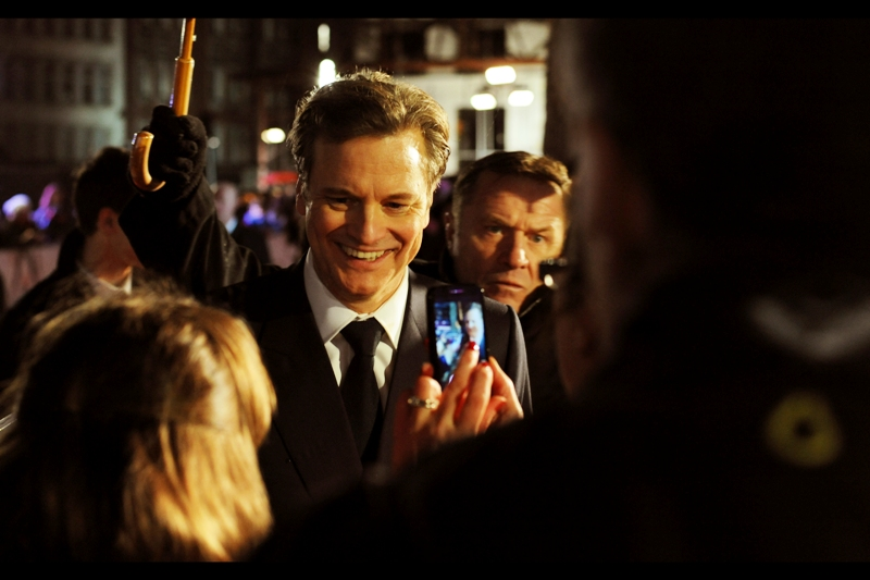It's not so much about the bemused smile on Oscar-Winning actor Colin Firth as it is the look of confusion on the guy behind him