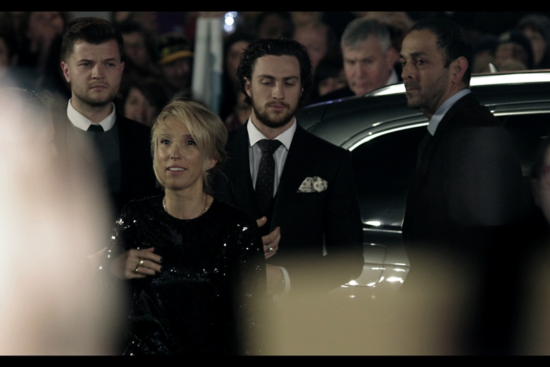 "The next arrival is director Sam Taylor-Johnson, and (behind her) actor Aaron Taylor-Johnson, who is not in this film but was Kick-Ass in the movie ""Kick-Ass"" and its sequel. I notice his suit jacket contains a handkerchief with polka dots. Meanwhile, my beanie is black and contains a 'thinsulate<tm>' logo. It's discreet, though.."