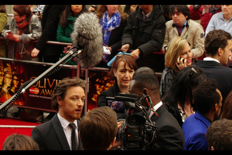 """Somebody shouted """"Brian May!!"""" but I've seen both him and his hair in the past, and I suspect they've mistaken the furry boom mike for the guy. Also : being interviewed, James McAvoy, nominee for best Actor at these awards."""