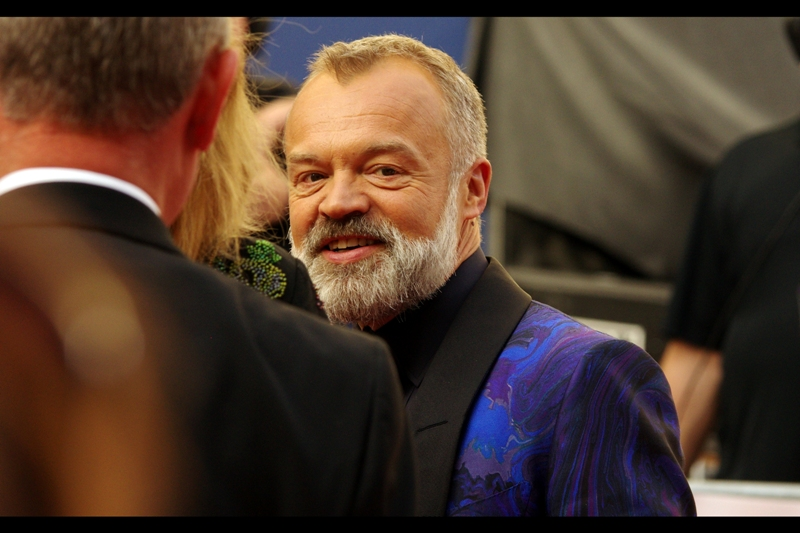 And I know this is Graham Norton because among Men In London, only he and director Terry Gilliam wear jackets and/or capes and/or bathrobes this silky or shiny to events. And this is not Terry Gilliam
