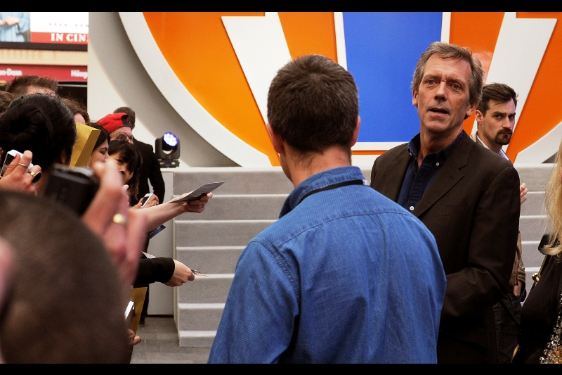 """I really liked Hugh Laurie in the excellent TV Series """"House"""", but I feel despite his charm, character and good humour, this photo belongs to the security dude in the background behind him to the right.. who potentially has not one of those things."""