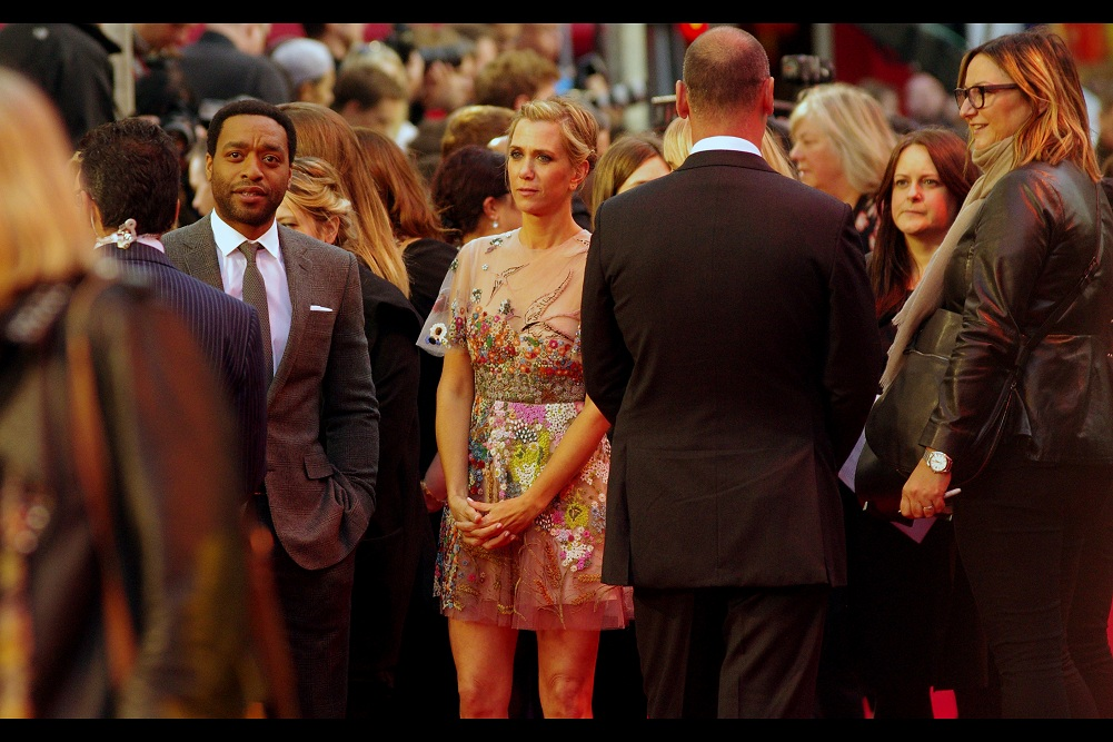 """""""Conversation pause getting awkward. Help me out here, bro?"""".  Chiwetel Ejiofor and Kristen Wiig find a temporary lull in the red carpet's frenetic activity."""