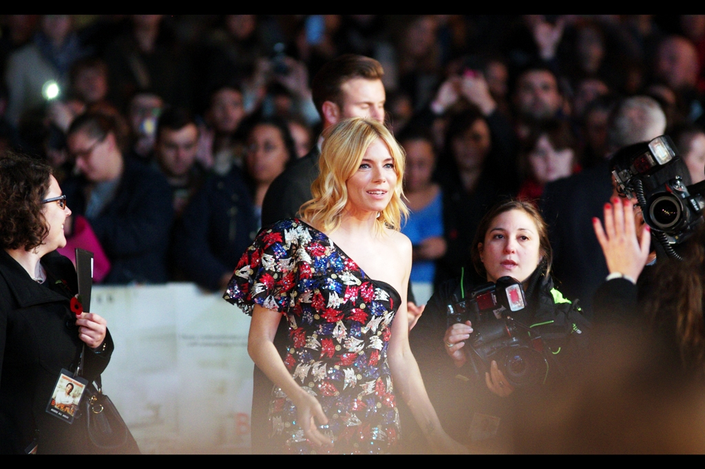 """Finally... and excitingly, the movie's female lead Sienna Miller arrives, wearing what can only be described as a dress (?). I last photographed her at  the Tom Hiddleston-dominated premiere of """"High-Rise""""  a few weeks ago during London Film Festival. And  'Foxcatcher' at the BFI LFF the year before that ."""