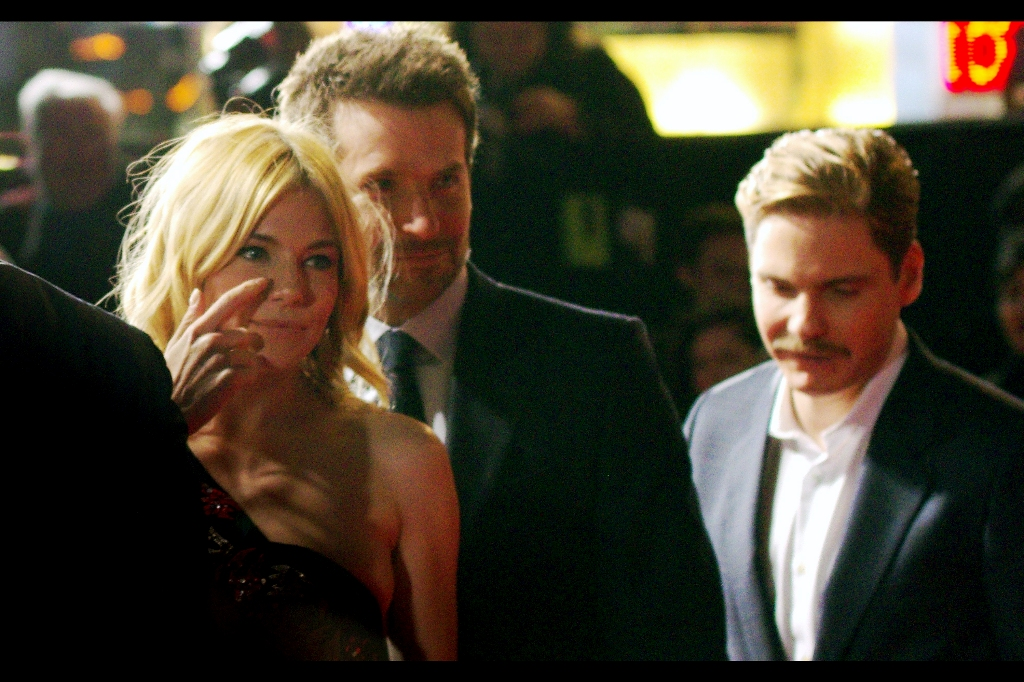"""""""Everyone keeps talking about how excellent the low-light capabilities of modern cameras is... so why am I still being blinded by press photographers and their damn flashes at every premiere??""""  Sienna Miller, Bradley Cooper and Daniel Bruhl grab a brief respite from the onslaught."""