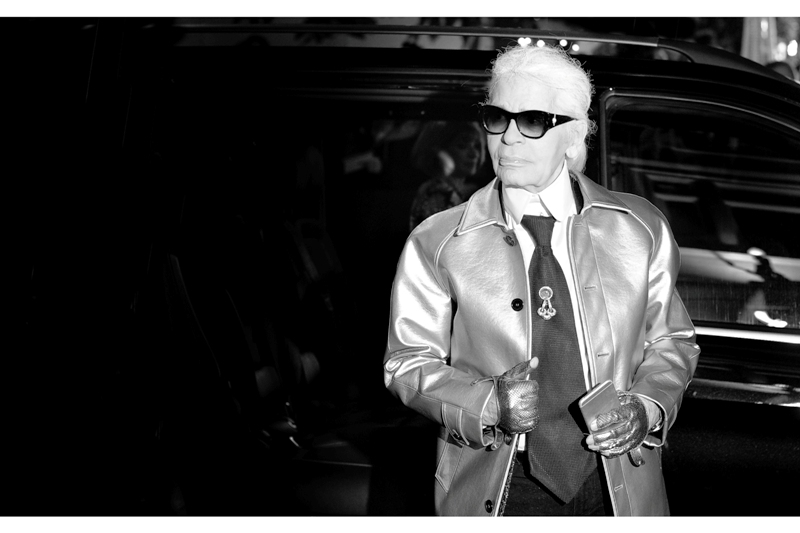 """"""" That thing in my tie? It's called a ' No,   I have no idea what it is, but I'm Karl Lagerfeld and I'm making it into a thing ' thing """". Also : in darkness, in background, and blurry : American Vogue editor Anna Wintour."""