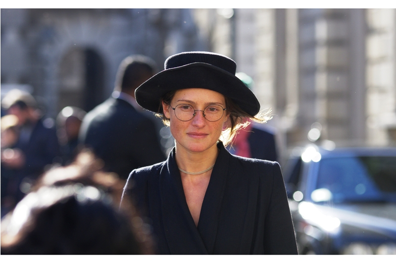 I think she's a designer, so in order to protect whatever faint hope I have of ever getting INTO one of the shows, I think she looks lovely, and the hat and glasses really suit the style she's going for (hopefully that of 'designer, fashion shows' and not 'Amish Winter Collection')