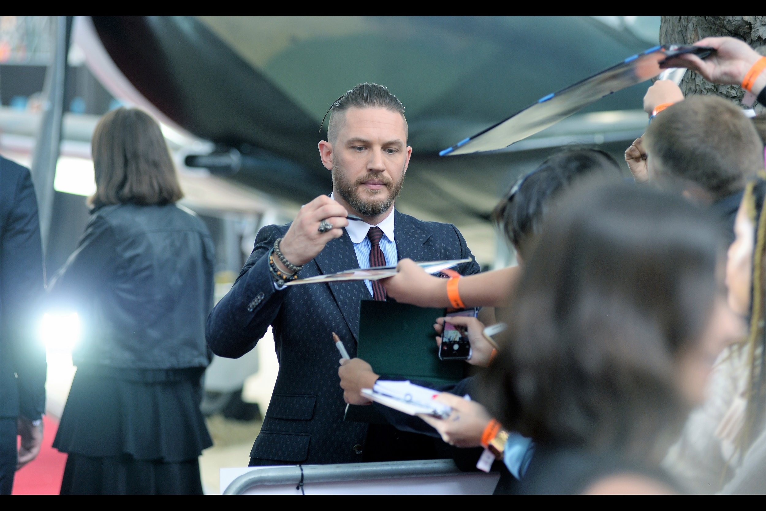 Tom Hardy is signing autographs while at least a third of the girls maintain a watchful eye on the spot where Harry Styles is currently being interviewed, waiting for the slightest twitch upon which to regenerate their excitement.