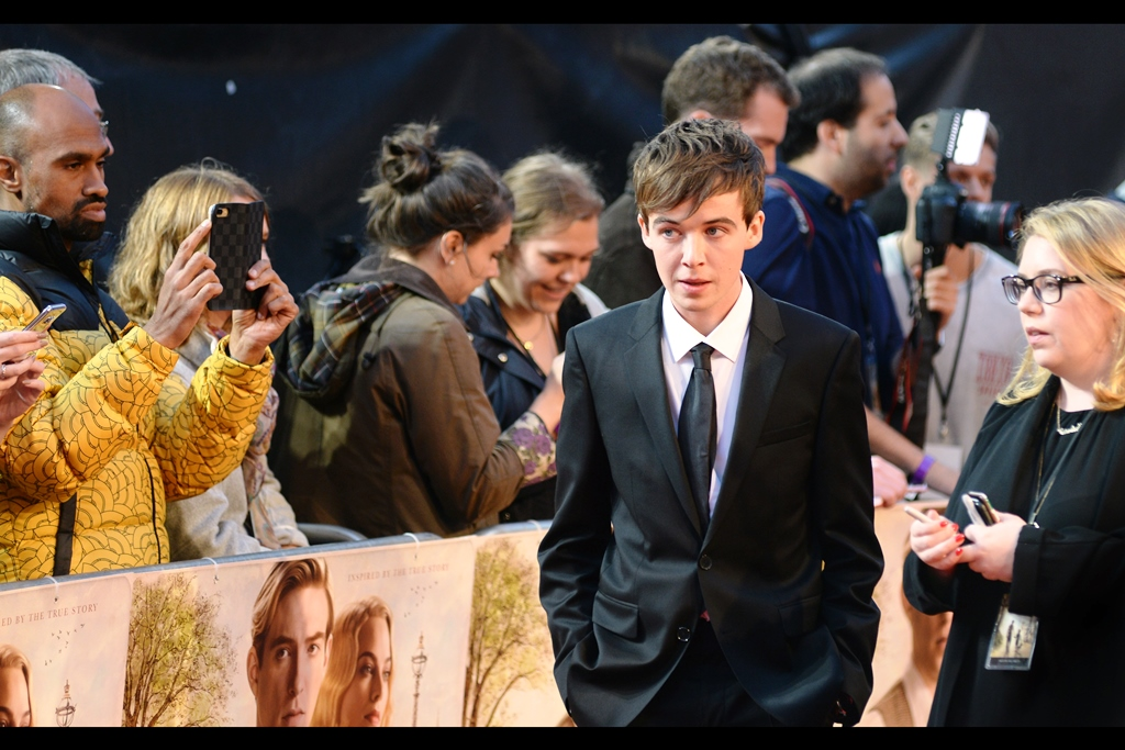 """That Yellow jacket that dude is wearing is awesome..."" ""I know."" ""And you made me wear a suit and tie..."" ""I know.""  Alex Lawther has a second ""Young <insert name of character>"" to his credit besides a slightly older Christopher Robin in this movie - he was also 'Young Alan Turing' in   'The Imitation Game'  ."