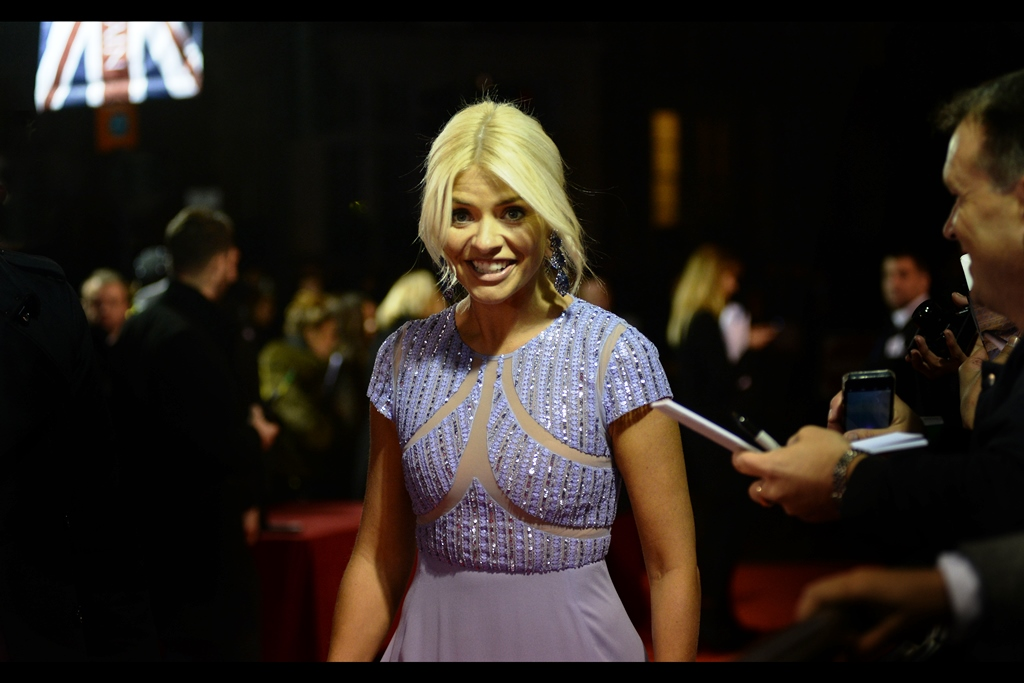 Holly Willoughby....? I think? I'm a bit more confident labelling the colour of her dress as a mauve/lavender than stating precisely what it is she does. I think perhaps she hosts something. TV show. Assuming TV is still a thing.