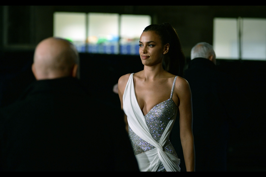 """""""Why is everyone here dressed so poorly in comparison to me?""""  Irina Shayk is a model, and my brain is trying to figure out how that sash of hers works three-dimensionally. Does it curl around the top and the bottom in some kind of moebius strip?"""
