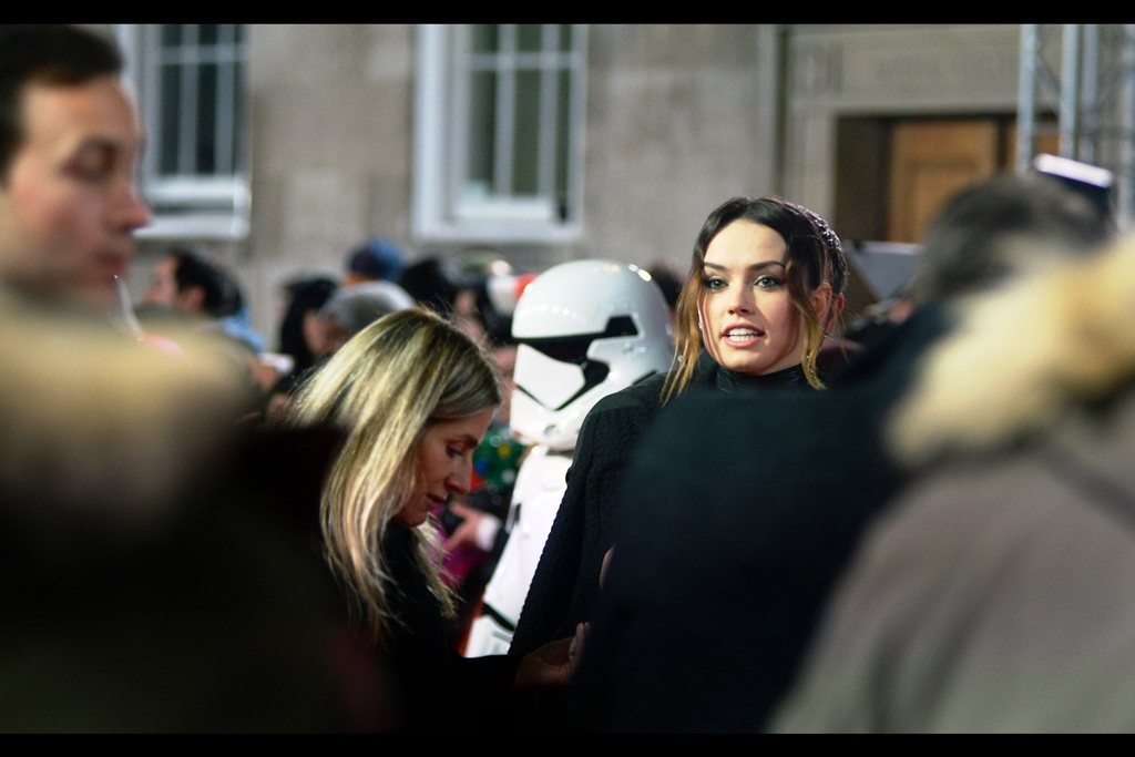 """What if I brought a whole bunch of photos and asked you to sign them. Would you do that?""  - Daisy Ridley is certainly appropriately dressed for this premiere, and the phalanx of attendants surrounding her probably block much of the chilly breeze, too."