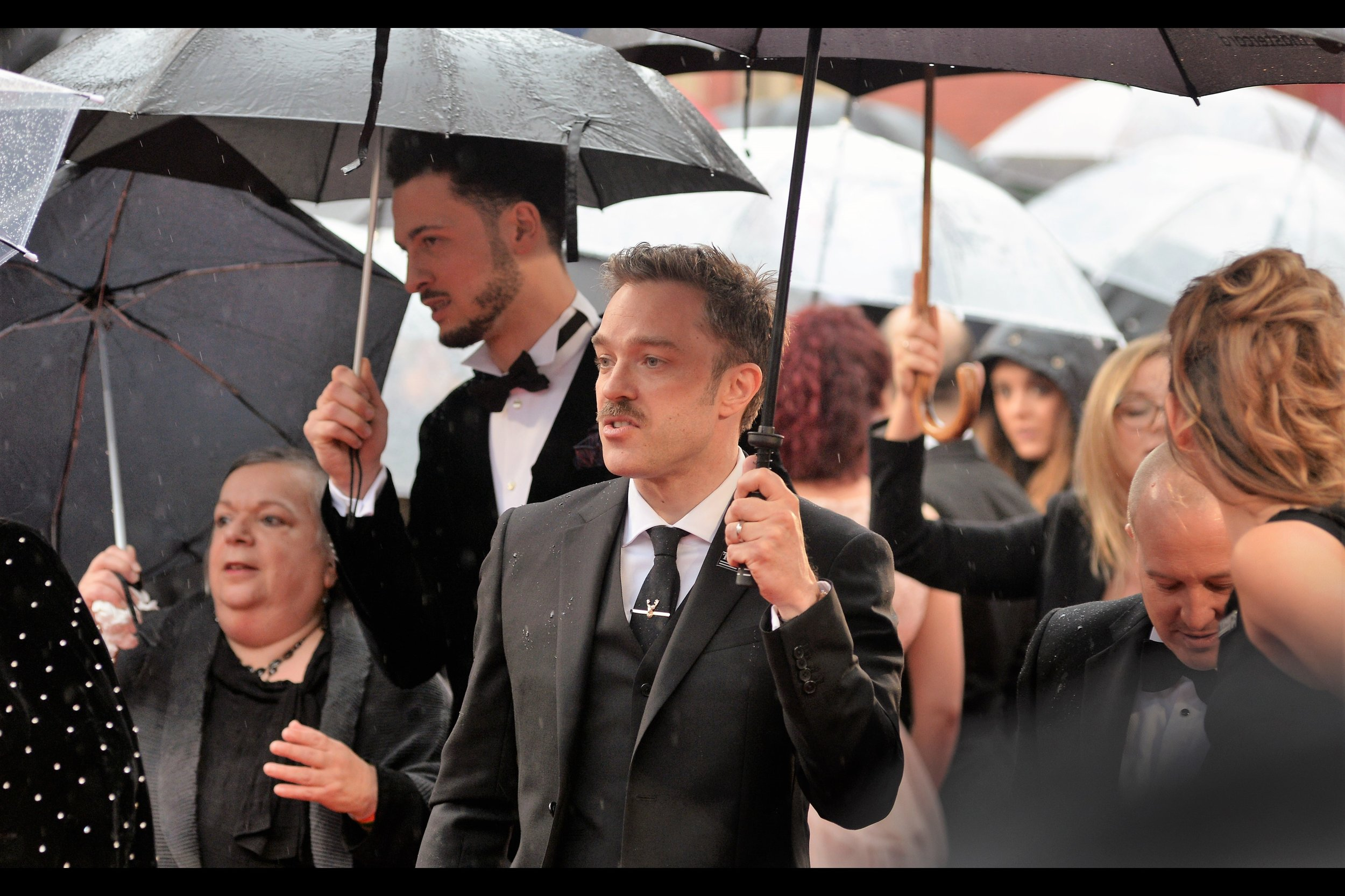 Added later : still unidentified, but I'm doubling down on Man With Moustache Holding Umbrella And Semi-Excitable Woman In Background.