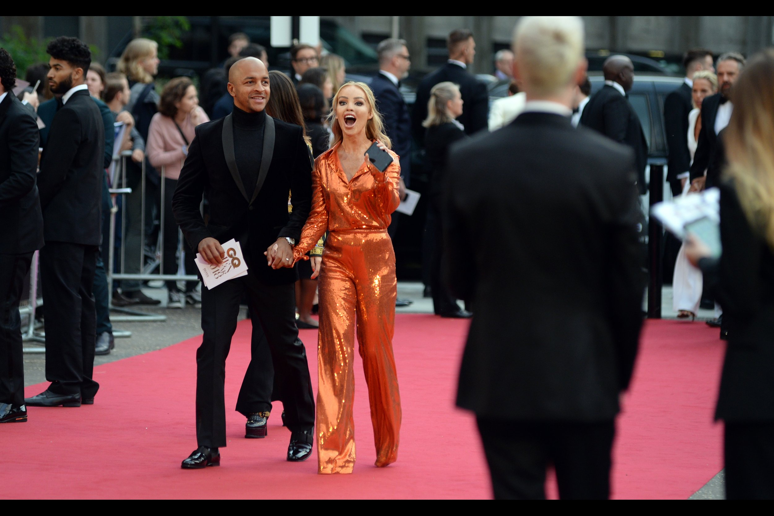 """I heartily endorse this phone I'm holding!!! Do I know the brand? Erm... no? Maybe Nokia? Do they still make phones?""  This is Katie Piper. Nature of fame unknown, but Colour of Jumpsuit should be determined pretty soon(ish)."